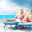 Rear view of a couple on a deck chair relaxing on the beach — Stock Photo #6370658