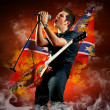 Rock guitarist play on the electric guitar around fire flames — Stok fotoğraf