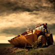 Foto Stock: Yellow tractor on golden sunrise sky