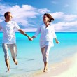 Foto Stock: View of happy young couple walking on beach, holding hands.
