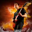 Rock guitarist play on the electric guitar around fire flames — Stock Photo #6370923