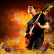 Rock guitarist play on the electric guitar around fire flames - Stockfoto
