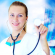 Smiling medical doctor with stethoscope on the hospitals backgro — Stock Photo