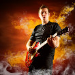 Rock guitarist play on the electric guitar around fire flames — Stockfoto
