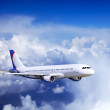 Airplane at fly on the sky with clouds — Stock Photo #6371047