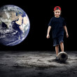 Child football player and Grunge ball on the dark background - Stock Photo