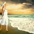 Young beautiful women in the white on the sunny tropical beach — Stock Photo #6371170