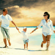 View of happy young family having fun on the beach — Stock Photo #6371179