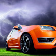 Beautiful orange sport car on dark sky with lightning — Stock Photo