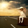Little girl waiting on the road with her vintage baggage - Stockfoto