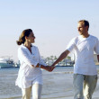 View of happy young couple walking on the beach, holding hands. — Stock Photo