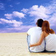 Young couple seating in desert in sunny day — Stock Photo