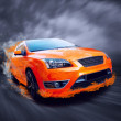 Beautiful orange sport car in fire — Stock Photo