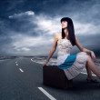 Royalty-Free Stock Photo: Young woman waiting on the road with her vintage baggage