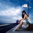 Girl waiting train on the platform of railway station — Stok fotoğraf