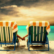 Rear view of a couple on a deck chair relaxing on the beach — Stock Photo #6371673