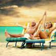 Rear view of a couple on a deck chair relaxing on the beach — Stock Photo #6371675