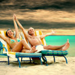 Rear view of a couple on a deck chair relaxing on the beach — Stock Photo #6371676