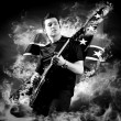 Rock guitarist play on the electric guitar around fire flames — Photo