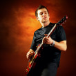 Foto Stock: Rock guitarist play on electric guitar, orange sky backgroun