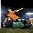 Foto Stock: Football player and jump of goalkeeper on field of stadium a