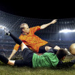 Stock Photo: Football player and jump of goalkeeper on field of stadium a