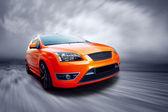 Schöne orange sport auto unterwegs — Stockfoto