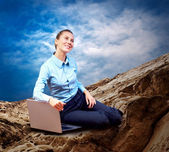 Happy Businesswoman seating with laptop on the mountain under bl — Stock Photo
