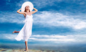 Young beautiful women in the white with pareo on the blue sky ba — Stock Photo