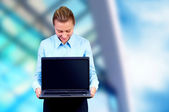 Happiness businesswoman with laptop on blur business architectur — Stock Photo