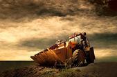 Altın gündoğumu gökyüzü üzerinde sarı traktör — Stok fotoğraf