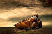 Yellow tractor on golden sunrise sky — Stok fotoğraf