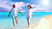 Vue d'heureux jeune couple marchant sur la plage, main dans la main. — Photo