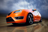 Beautiful orange sport car on road — Stok fotoğraf