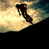 Silhouette of a man on muontain-bike, sunset — Stockfoto