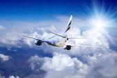 Avión a volar en el cielo con nubes — Foto de Stock