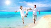 Widok szczęśliwą rodzinę młodych zabawy na plaży — Zdjęcie stockowe