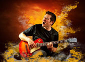 Rock guitarist play on the electric guitar around fire flames — Stock Photo