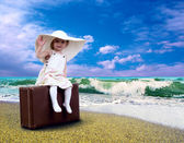 Young child with baggage on the tropical beach — Stock Photo