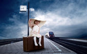 Little girl sitting on vintage baggage on the train platform of — Stock Photo