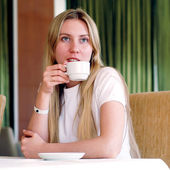 Happy woman in white with cup of coffee or tea. — Stock Photo