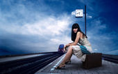 Girl waiting train on the platform of railway station — Стоковое фото