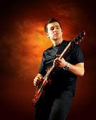 摇滚吉他手玩电吉他,橙色的天空艾菲尔铁塔的背景 — 图库照片