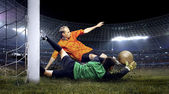 Football player and jump of goalkeeper on the field of stadium a — Stok fotoğraf