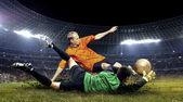 Piłkarz i skok bramkarza na boisku stadionu — Zdjęcie stockowe