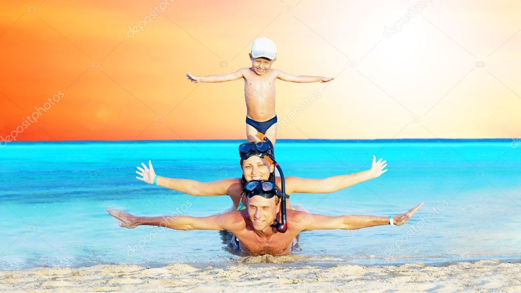 Happy young couple and son with snorkelling on a sea beach — Stock Photo #6370312