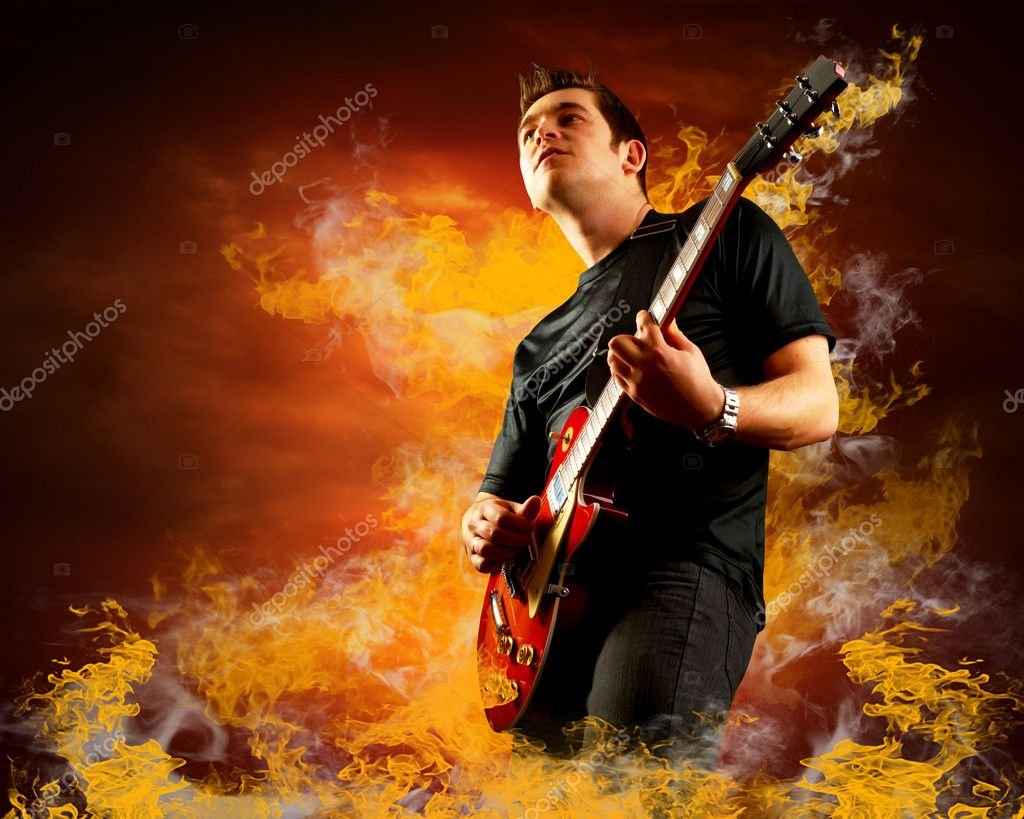 Rock guitarist play on the electric guitar around fire flames  Stock Photo #6370924