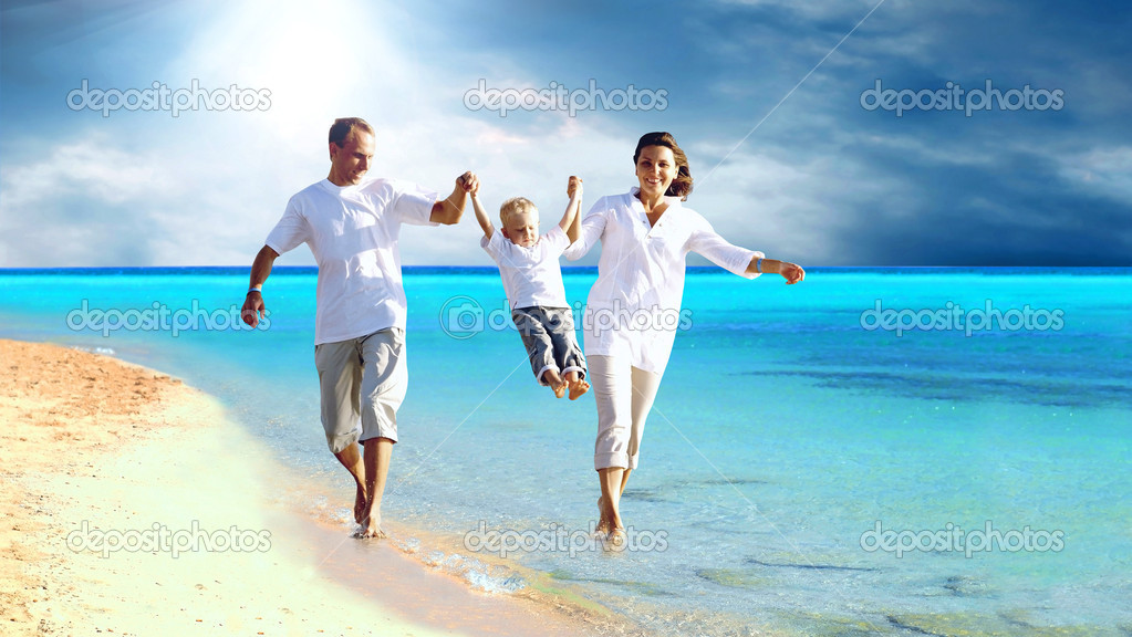 View of happy young family having fun on the beach - Stock Image