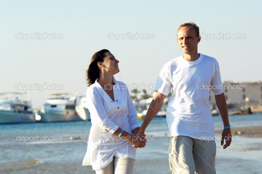 View of happy young couple walking on the beach, holding hands. — Stock Photo #6371429