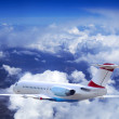 Airplane at fly on the sky with clouds — Stockfoto